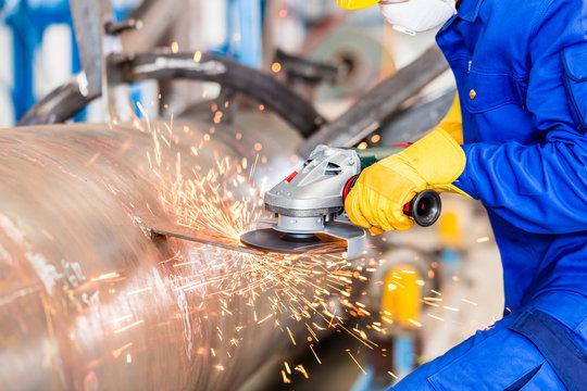 Industrial worker in factory grinding metal