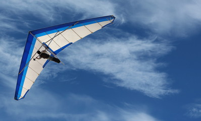 Hang Glider – Hang Glider flying in the sky on a bright blue day