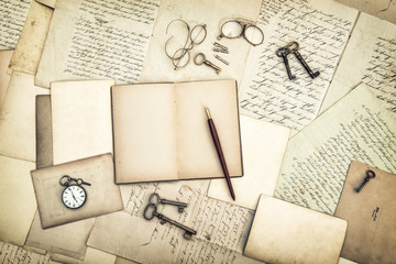 Open diary book, vintage accessories, old letters and postcards