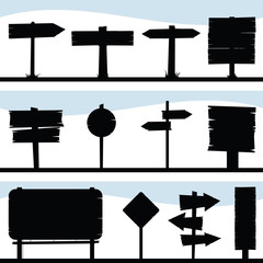 A set of a variety of silhouette signs on signposts including arrow pointing signs.