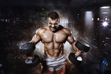 Athlete muscular bodybuilder in the gym training with dumbbells Wall mural