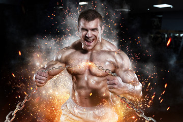 Athlete muscular bodybuilder man emoticon tear chain in the gym Wall mural