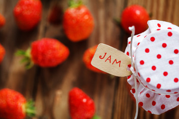 Top view on jar of jam with strawberry on wood and noties on wood background