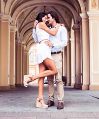 Vertical shot of a happy beautiful couple having fun in the european city