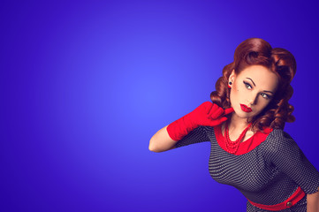 Red hair beautiful curious pin-up girl on a blue background with copy space