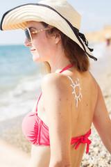 Sunscreen lotion over tan woman skin with birthmarks