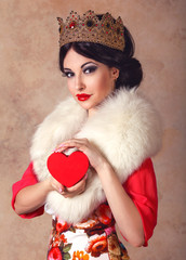 Beautiful brunette woman in golden queen crown and white fur collar holding a heart in her arms