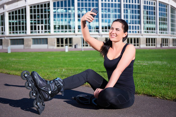 happy woman in roller skates sitting and making selfie photo on