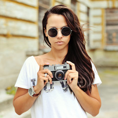 Beautiful girl photographer with old camera