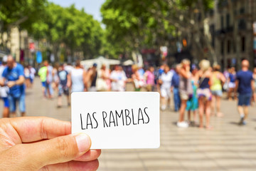 man shows a signboard with the text Las Ramblas, at Las Ramblas