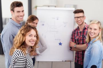 gruppe studenten steht vor einem flipchart und erarbeitet ideen