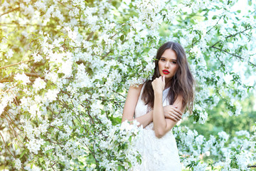 Portrait of young beautiful woman in spring blossom trees.