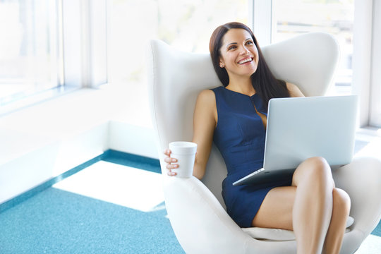 Portrait of relaxed business woman in office. Relax and freedom