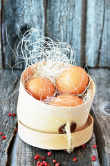 Three eggs in the wooden box with red pepper on the vintage background