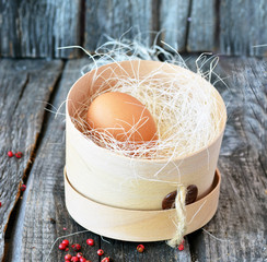 Orange egg in the wooden box with red pepper  on the vintage background