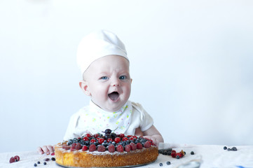 Funny newborn confectioner with berry biscuit cake.
