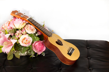 Ukulele and beautiful flower on leather arm chair