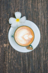 Top view of offee cup and flower on old wooden background