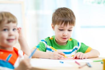 little preschool boys drawing at nursery
