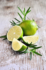 Fresh green lime and rosemary herb on wooden background, selective focus
