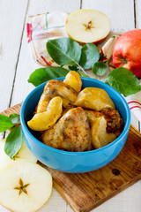 Baked chicken with apples in a bowl on a wooden table