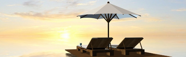 Deck Chairs and umbrella in sunset on the beach