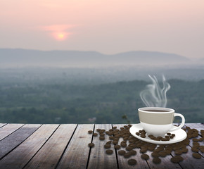 Cup with coffee on table over mountains landscape with sunrise