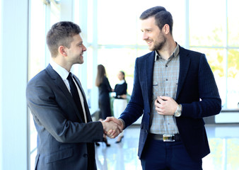 businesss and office concept - two businessmen shaking hands