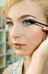 Make-up artist applying mascara  on model's eye, close up