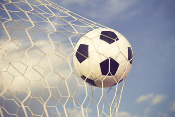 soccer ball in the net on blue sky background vintage color