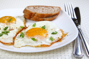 Fried eggs on the white plate, shallow focus