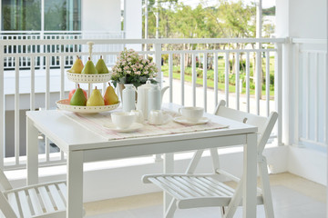 beautiful terrace with white furniture and tea or coffee set at