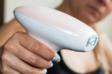 young blond woman holding a appliance for photo-epilation