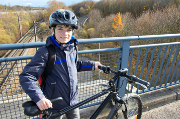 Boy with bicycle and helmet. Smiling kid with black helmet and his bicycle on a bridge.