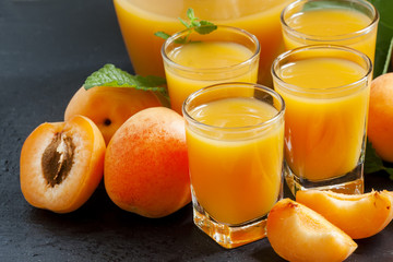 Fresh apricot juice and apricots with mint on black background,