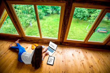Woman working on the floor in wooden house
