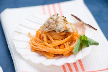 Spaghetti con vongole  e sugo al pomodoro conditi nella conchiglia