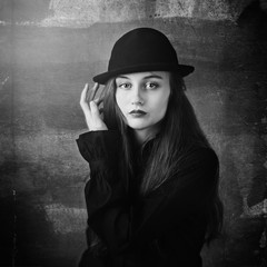 Black and white portrait of a young beautiful girl in a hat.