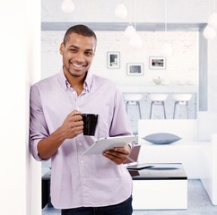 Happy young man standing at home holding tablet