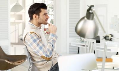 Young man thinking at home