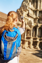 Female tourist with smartphone taking picture in Angkor temple