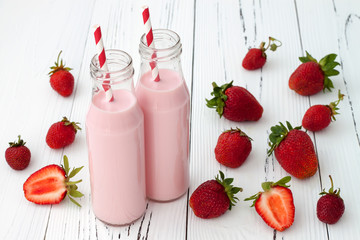 Strawberry milk in traditional glass bottles with straws on old vintage wooden background