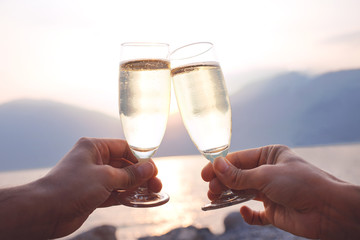 Lovers toast with wite wine at sunset