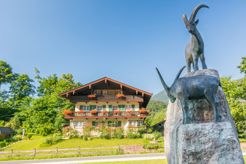 Steinbock-Statue vor traditionellem Landhaus