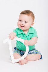 8 month year old baby sits on a white background holding a white letter D looking at camera smiling. dressed in a cute green polo shirt and blue plaid shorts.