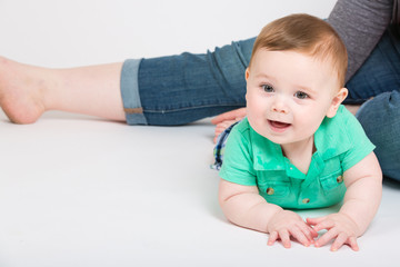 8 month year old baby lays on his stomach looking towards camera, while mom is sitting in background. dressed in a cute green polo shirt and blue plaid shorts.