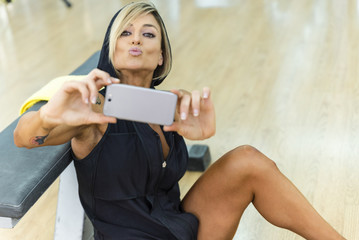 Sports beautiful woman making selfie on smartphone at gym.
