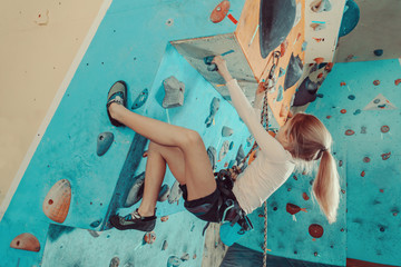 Girl in safety equipment climbing indoor