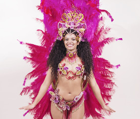 Brazilian samba dancer wearing traditional pink costume and smil