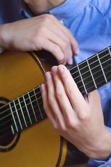 Acoustic guitar's fretboard and young male's hands